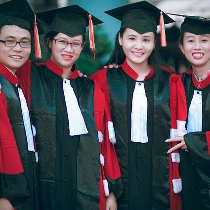 Man and women wearing red and black academic gowns and black 1699414