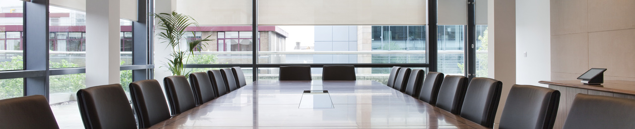 Conference room brown laminated particle board conference desk dark brown leather wrapping chair white stained concrete pillar black aluminium frame clear glass window white stained ceiling