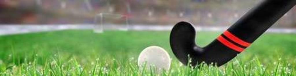 95512279 field hockey stick and ball on grass in brightly lit outdoor stadium with focus on foreground and sh